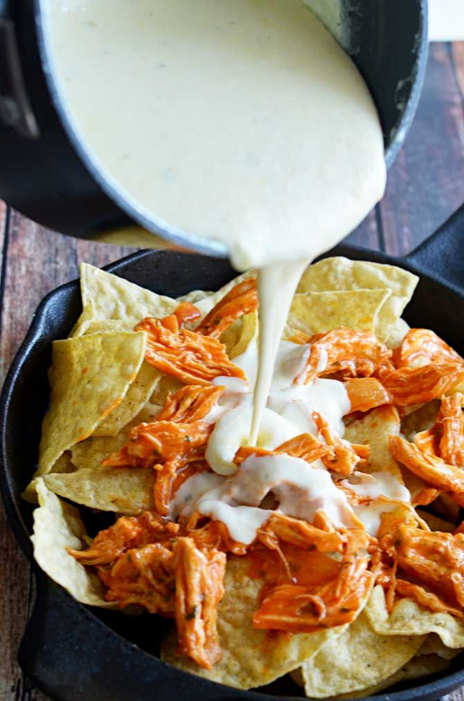 Loaded Buffalo Chicken Nachos.  Shredded buffalo chicken, cheesy ranch queso, blue cheese crumbles, pickled jalapenos, and chopped green onions | hostthetoast.com