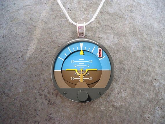 Pilot Jewelry - A cool pendant featuring an attitude indicator, one of the most important little gizmos in a cockpit! 1 inch (25mm) diameter pendant. Use coupon code TWOFOR25 during check-out to save $5 on any two pendants :D  Your eye-catching glass pendant starts as a crystal clear domed glass cabochon. The high-definition laser printed digital image is securely bonded to the reverse side of the glass using a multistage process, rendering a 3-dimensional effect. Pendants are sealed with a…