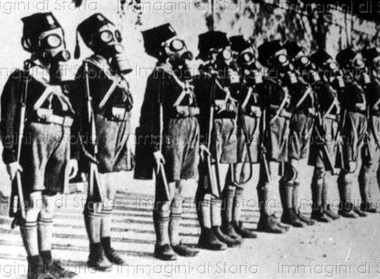 """Young Balilla members wearing gas masks-Origins- Nationalists in the years after the war thought of themselves as combating the both liberal and domineering institutions created by cabinets such as those of Giovanni Giolitti, including traditional schooling. Futurism, a revolutionary cultural movement which would serve as a catalyst for Fascism, argued for """"a school for physical courage and patriotism"""", as expressed by Filippo Tommaso Marinetti in 1919. Marinetti expressed his disdain for…"""