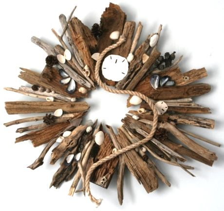 A #driftwood sunburst wreath that has other beach finds glued to it. One of the top 8 beach craft ideas on Completely Coastal.