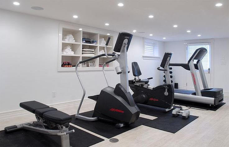 Walk out basement home gym boasts a treadmill, spinning cycle, elliptical and a work bench placed in front of inset shelving filled with gym accessories.