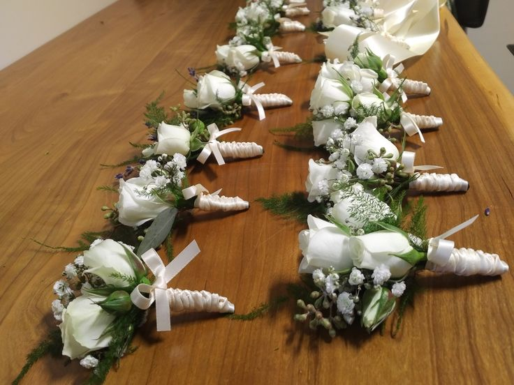 Boutonnieres and Corsages for the bridal party and special people.  whites, baby's breath, spray roses, lavender, hypericum berries, satin ribbon, braiding up the stems.  Perfection