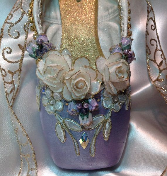 This exquisite purple and gold decorative pointe shoe reflects the ballet aesthetic. The delicate paper roses have been tipped in gold and