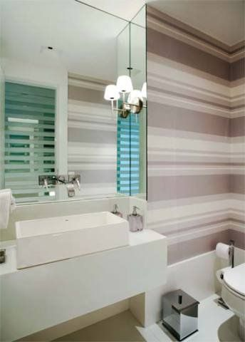 """O papel de parede em tons neutros, com estampa de listras horizontais, foi a solução proposta pela arquiteta carioca Roseli Muller para ampliar visualmente o lavabo de apenas 2,10 m². """"Essa padronagem combinada com o branco do piso e da bancada de marmoglass, faz com que o ambiente pareça ser maior do que é"""", explica Roseli. O espelho com arandelas nas laterais também contribui para aumentar o espaço."""