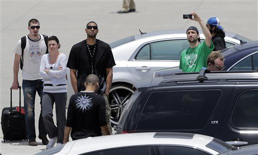 San Antonio Spurs' Manu Ginobili, right, takes photos of fans as he stands with teammates Tim Duncan, center, and Tony Parker, back to camera, as they return home after losing to the Miami Heat in the NBA Finals basketball game, Friday, June 21, 2013, in San Antonio.