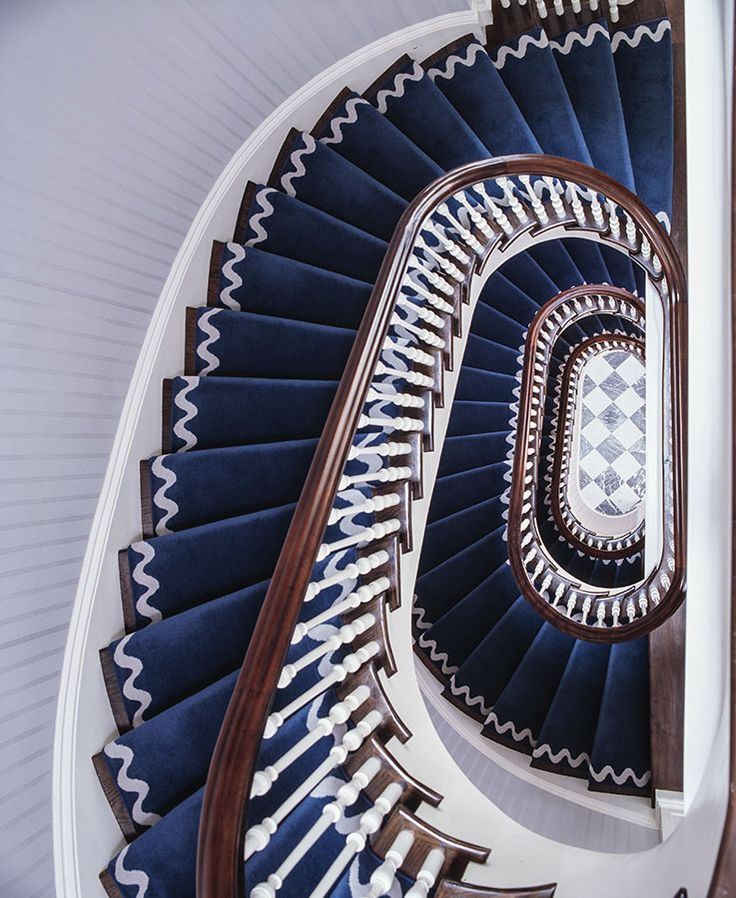 """ric-rac"""" detailing on the navy stair-runner curling around this spiral staircase by Anthony Baratta"""