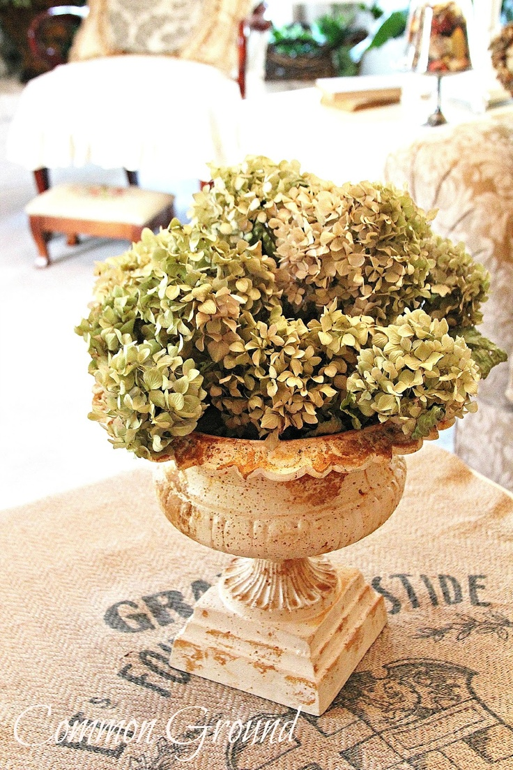 Dried hydrangea blooms, arranged in a weathered urn, bring charm to any table.