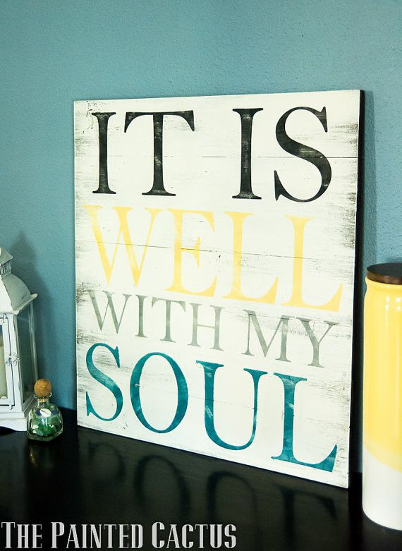 """This pallet style sign measures approximately 19"""" wide and 21.5"""" tall. The sign shown is made with black, yellow, grey, and teal lettering. It is a cream distressed background with brown undertones. T"""