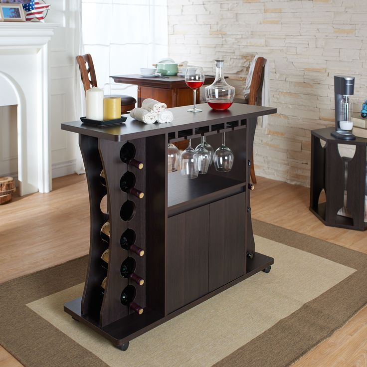 Display your wine collection within this unique, space-saving bar addition. The freestanding structure features caster wheels, hanging glassware racks, an enclosed cabinet, and open slots to hold up to twelve standard-size wine bottles.