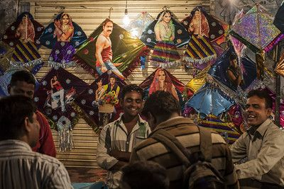 Colourful kites with photos of Bollywood actors in the night market or Indian bazaar for the festival of Makar Sankranti or Uttarayan in the old area Khadia of Ahmedabad in Gujarat, India.