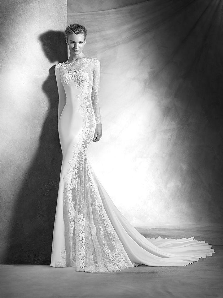 veda, collectie 2016 Weergaloos mooi en chic deze trouwjurk van soepel vallende materialen. De jurk is in tweeën gedeeld met een gesloten rechterkant. Super mooi maar ook heel gedurfd zoals de transparante kant over de hele linkerzijde is verwerkt.  Prachtig in combinatie met de off shoulder, de lange doorzichtige mouw en rugpand.  #exclusief #glamour #zijde #couture #atelierpronovias #koonings
