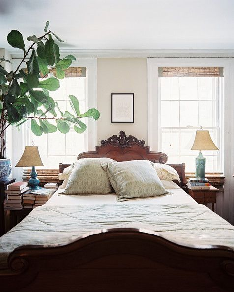 Bedroom Photo - An antique wooden bed situated between two windows