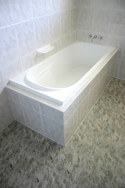 White Bath with Grey Bathroom Tiles - Bathroom Renovations Brisbane