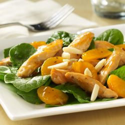 Ensalada de Naranja y Espinaca con Pollo: El pollo con salsa de miel y naranja se destaca sobre la espinaca fresca con naranjas mandarina y almendras crujientes