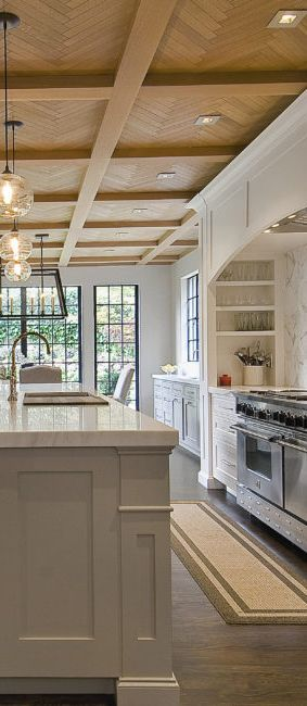Modern, warm and inviting kitchen design with wood ceiling and floors, white cabinets and blue star range.