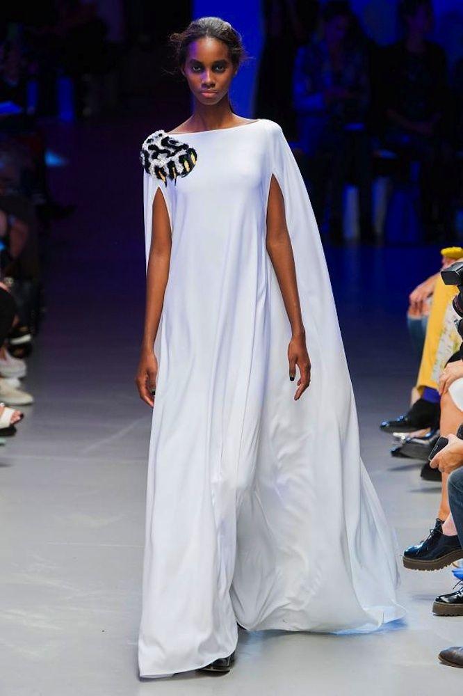 Vestidos de pasarela para novias no convencionales. Giles. Vestido largo muy fluido en color blanco con capa a juego. Como único detalle lleva en el hombro un abalorio bordado con lentejuelas de colores.