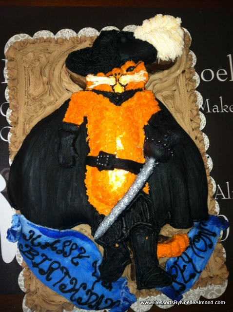 Storybook Puss n Boots Cake in 3 D with flowing fondant cape, hat, boots and belt with hand painted detail. Hand piped feather and cat body with shaped sword and embelishment. Storybook Scroll Birthday Wishes with a Brownie Crust Cake and Double Chocolate Frosting. www.DessertsByNoelleAlmond.com