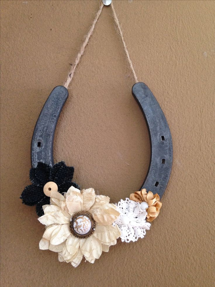 Horseshoe wall hanging. Easy to make and inexpensive. All you need is hot glue, twine, fabric flowers (I bought mine at Hobby Lobby), and horseshoes (can be bought at any farm store or from someone who shoes horses). Just glue the twine on the back side of the shoe in the groove and arrange your flowers how you'd like and there you go. Please note that I used a high temp glue.