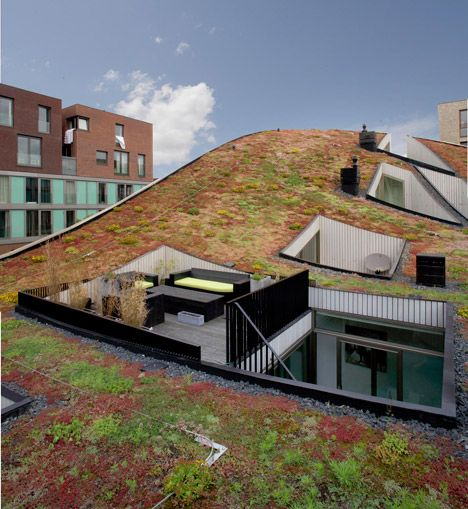 Assorted plants create a blanket of red and green across the undulating roof of this housing block, completed by NL Architects for a newly developed Amsterdam neighbourhood