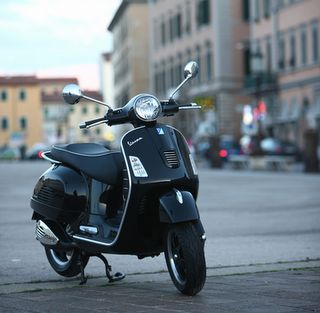 Modern Vespa, black, somewhere in Italy.