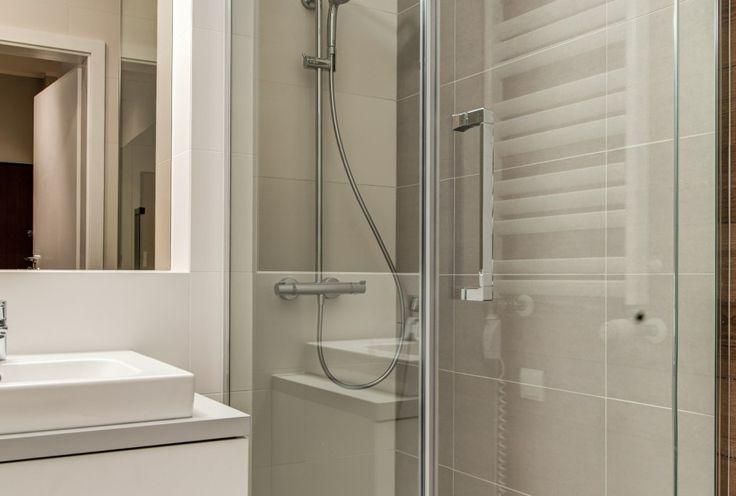 Aranżacja wnętrza łazienki z prysznicem. Prysznic z szklaną szybą i odpływem liniowym.