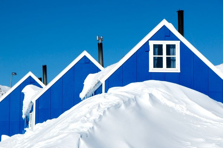 Some of the newer houses in Ittoqqortoormiit, the most northern settlement on the East coast of Greenland.  In winter the front door is often covered by meters of snow and it is not unusual for the top floor window to be used as entrance/exit.  Blue by Nicole Cambré, via 500px