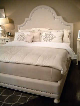 Nailhead trim throughout the profile of the bed