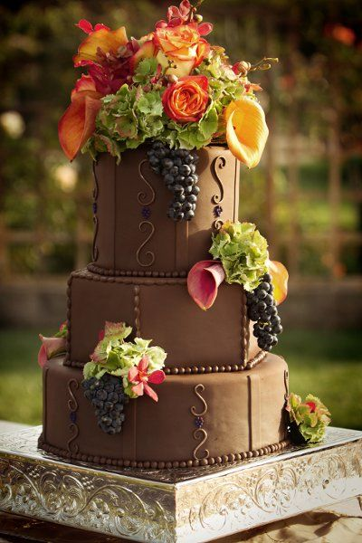 """Fall inspired wedding cake. 13, 10 & 7"""" mixed tiers covered in dark chocolate fondant. Cake flavors were fresh banana, blackberry/cabernet wine & almond apricot with differet flavors of Italian Meringue Butter Cream. Scrolls & bead trim highlighted with edible copper luster dust. Fresh flowers & local Cabernet Savignon Wine grapes look striking against the chocolate fondant."""