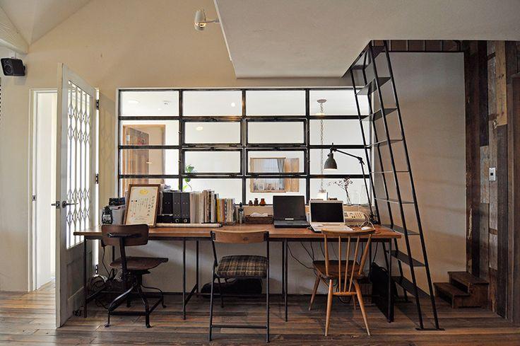 リビングと吹き抜けの階段部分は、スチール枠の窓で仕切られている。その横にはロフトに上がるスチールの階段も。木の床とスチールのコンビネーションが美しい。