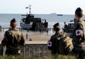 """6-Jun-2014 9:59 - LANDING HERDACHT BIJ ZONSOPGANG. Op het strand van Normandië zijn vanochtend de mannen herdacht die op D-day als eersten aan land gingen. Om 6.30 uur herdachten honderden mensen op Omaha Beach de mannen van de 29ste Divisie van het Amerikaanse leger, die precies 70 jaar daarvoor naar de Normandische kust waadden. De vlaggen hingen halfstok. Soldaten en veteranen van de 29ste Divisie stonden om precies 6.30 uur in de houding. Daarna riepen ze hun motto """"29, let's go!"""" en..."""