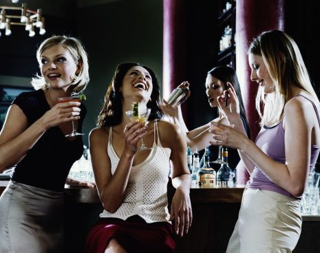 Three Young Women Drinking Cocktails At Bar Laughing Stock Photo 827375-003