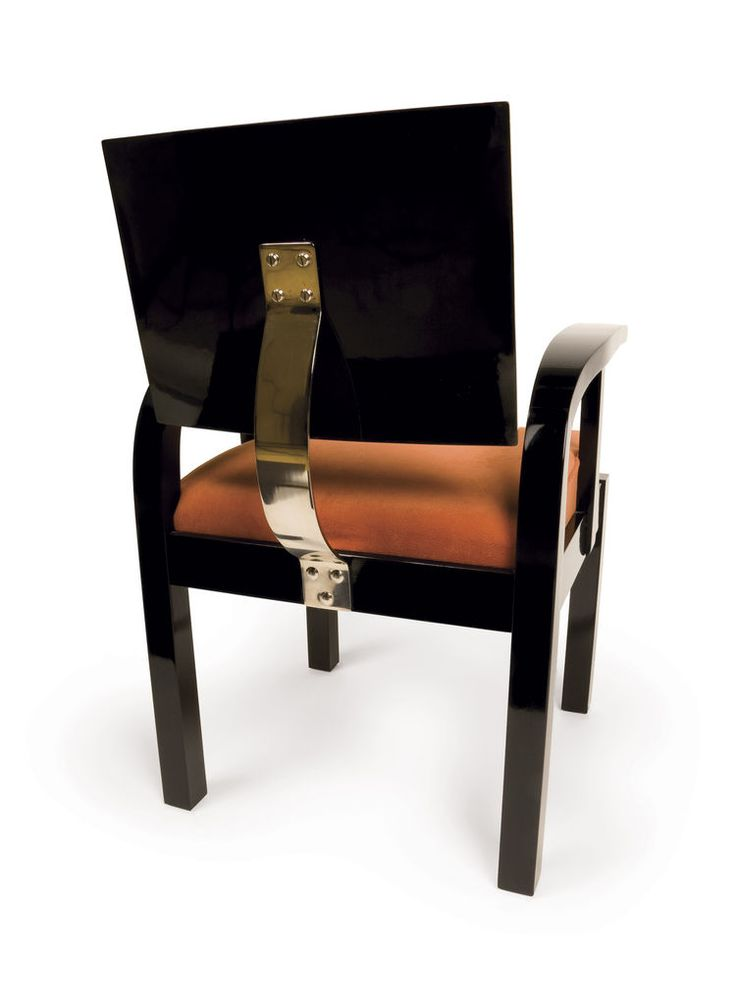 The armchair's back is suspended by a modern bent-chrome bar.