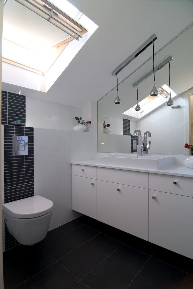 Tile behind the tankless toilet with small shelf for Small bathroom with sloped ceiling