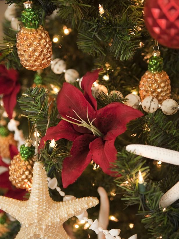 Coastal- and Cottage-Style Christmas Decorations: A South Pacific Christmas tree is adorned in starfish, pineapples and bright-red tropical flowers.  From DIYnetwork.com