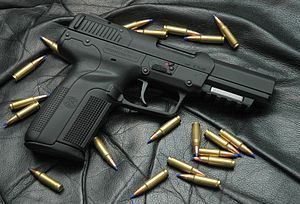Photo of an all-black Five-seven USG pistol surrounded by 5.7×28mm SS197SR cartridges