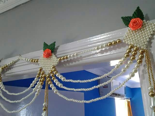 Pearls and Golden beads woven into an eye catching Toran / Vandanwar Cute little paper roses add to the beauty.