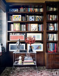 Books shelved the traditional way with colorful art sitting in front. Bookcase Style Ideas How To | Architectural Digest
