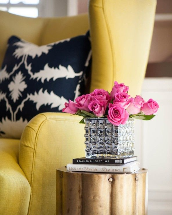 Cozy reading corner brightened by a yellow wingback chair accented with a black and white leaf pillow alongside a Arteriors Zeb Corrugated Antique Brass Accent Table topped with books and a square shaped crystal vase of pink roses.