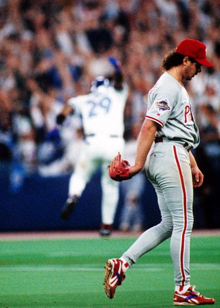 Pitcher Mitch Williams of the Philadelphia Phillies walks off the field as Joe Carter of the Toronto Blue Jays dances his way around the bases after hitting the Series-winning home run