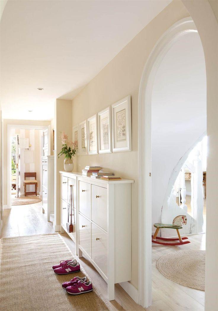 Pasillo con muebles zapateros, alfombra y cuadros