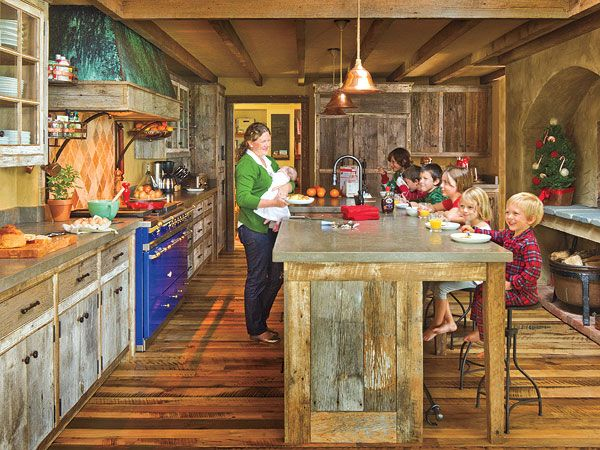Rustic Cabin Kitchen ~ This family kitchen in Charlottesville, Virginia, looks like the workspace in a rustic log cabin, only with modern appliances. The large beams and cabinet fronts are made of wormy chestnut barn siding. Iron hardware made by a local craftsman is used throughout the space.