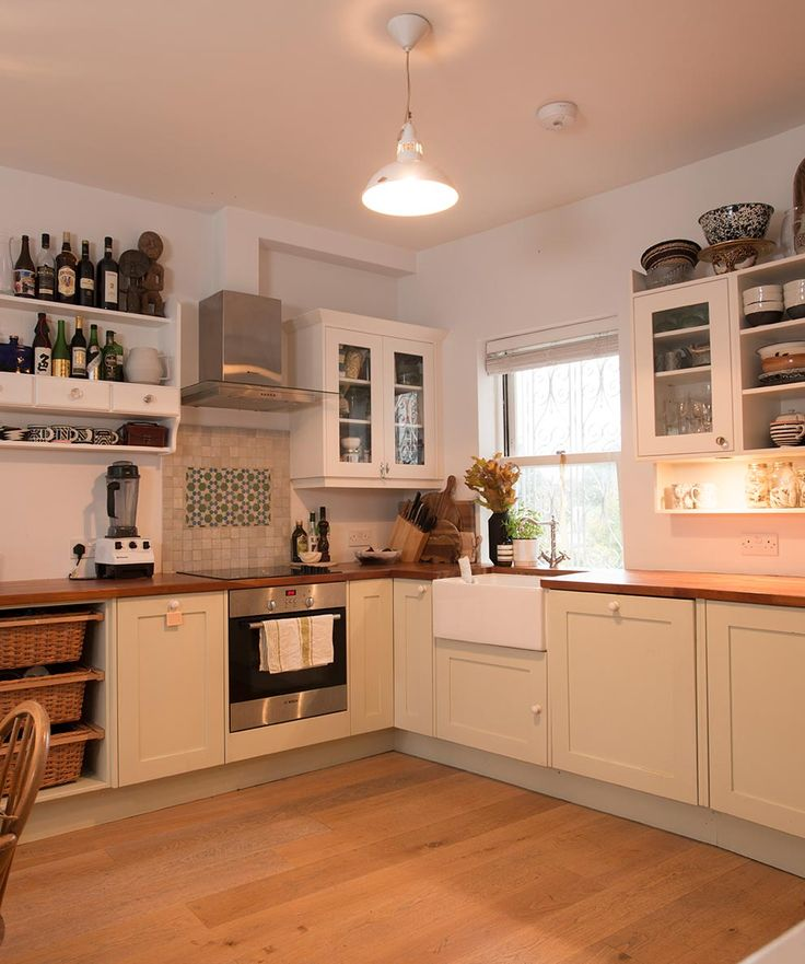 Cream and white kitchen units are paired with an oak wooden worktop and flooring, whilst bottles and tins are stacked on shelves
