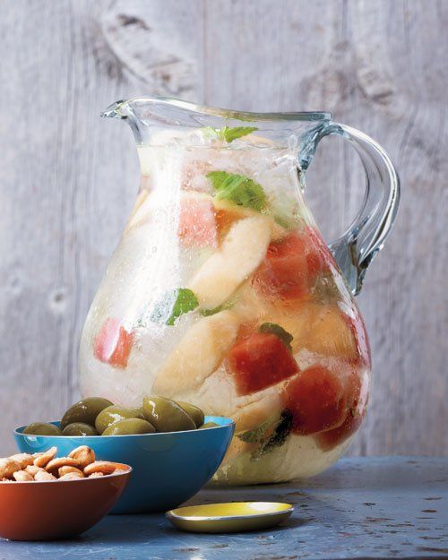 1/2 honeydew melon  1 pound seedless watermelon, peeled and cut into 1-inch pieces  1 pound cantaloupe, peeled, seeded, and thinly sliced  1 cup fresh mint leaves  1 bottle (750 ml) dry white wine, such as Sauvignon Blanc  1 liter chilled ginger ale  Ice
