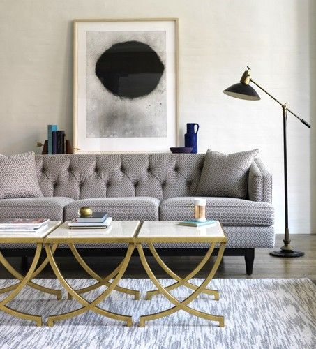 grey couch, brass and marble coffee table wood maybe
