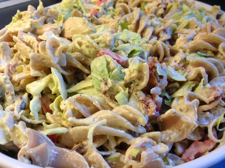 Til 5 personer: 1 stekt kylling (eller to stekte kalde kyllingfileter, ha de i sølvfolie i ovnen så blir de ikke så tørre) 2 porsj (400 gram ukokt) pasta. Bruk gjerne: penne(rør)/fusilli(skruer)/farfalle(sløyfer) eller annen pasta med artige fasonger. 1/2 pose pinjekjerner 1 boks creme fraiche 1/2 rød paprika 1/3 purre (bruk kun av det hvite) 2 fedd hvitløk (et fedd er det noen kaller en båt, men på hvitløk heter det fedd) 1/4 isbergsalat 1-2 ss pesto 1 pk bacon