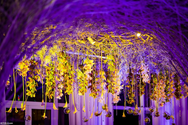 Hanging flower decor with ceiling covered with branches. Purple and green light.