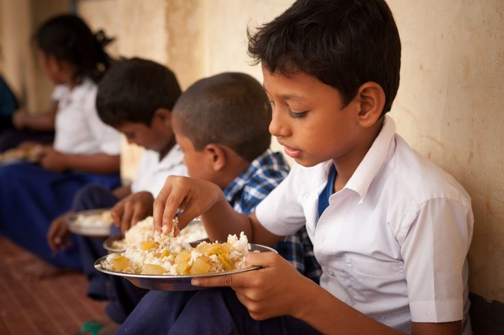 Children enjoying the mid-day meal in Mangalore government school. Children likes the food they get every day as it is healthy and nutritious food.