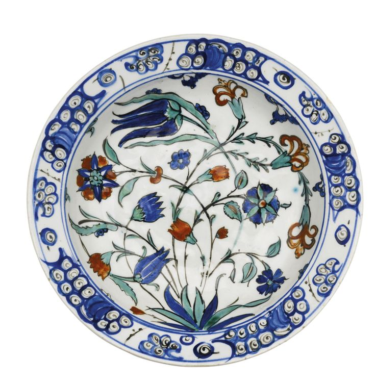 AN IZNIK POLYCHROME POTTERY DISH, TURKEY, CIRCA 1570 of rounded form, decorated in underglaze cobalt blue, viridian green and relief red with black outlines, with a leafy tuft from which springs interlacing tulips, irises and carnations, the rim with a breaking wave pattern, the reverse with alternating flowerheads and floral bunches