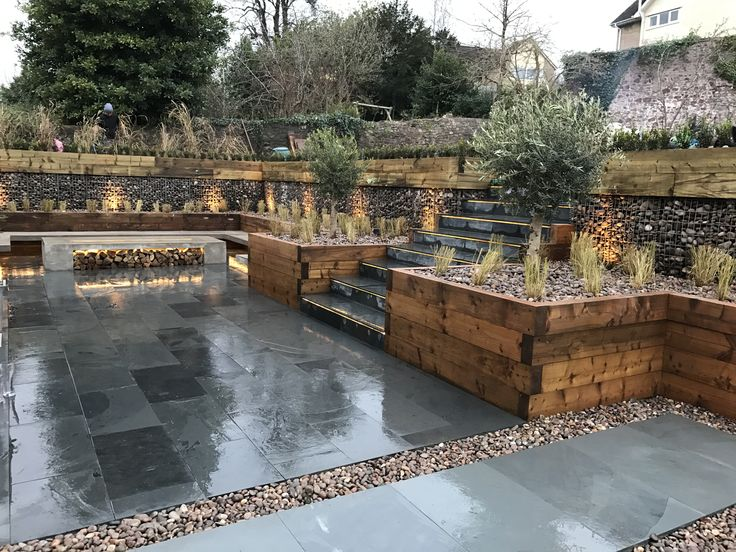 Beautiful multi level garden by Tranquilo Landscapes in Bristol, U.K. Polished concrete fire pit with wood store and floating benches. Down lit with LED strip lights. Highland pebble filled gabions and raised sleeper planting beds. Black slate. Olive trees. Pennisetum