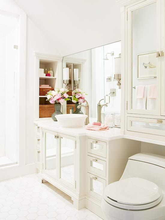 Bathroom Makeover -Smart space planning and chic updates elevated this once-nondescript powder room from drab to fab. Annexing a sliver of space from surrounding rooms paved the way for upgrading the powder room a full bath. Even with the added square footage, the room still lacked a window, but a white-on-white color scheme and plenty of reflective surfaces create an airy atmosphere